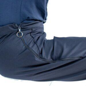 Dit ontwerp is speciaal ontworpen voor de zittende mens. De stof is huidvriendelijk en kan goed lichaamswarmte afvoeren, waardoor het niet gaat irriteren op de huid. De broek knelt niet om de buik. De achterkant van de broek is verhoogd en de broekspijpen extra verlengd. Er is voldoende ruimte in het zitvlak voor het niet zichtbaar dragen van incontinentiemateriaal. In het ontwerp is rekening gehouden met zo min mogelijk naden. De broeken hebben een rechte broekspijp die helpen bij makkelijker aantrekken. Bijkomend voordeel is dat het dragen van een spalk of urinezakhouder niet of nauwelijks zichtbaar is. Aan de voorkant zijn sierzakken opgestikt, zodat het er wel netjes en stijlvol uitziet. Doordat het sjorvast is, wordt aankleden door verplegend personeel of mantelzorg ook makkelijker. De broek kan worden uitgebreid met ritsen. Daarbij is de keus voor 2 korte ritsen tot ongeveer de heup.Daardoor wordt het makkelijker om incontinentiemateriaal te controleren of om naar de wc te gaan. Of 2 lange ritsen, waardoor het aankleden op bed veel makkelijker gaat en zowel broekdrager als hulpverlener fysiek minder belast worden.