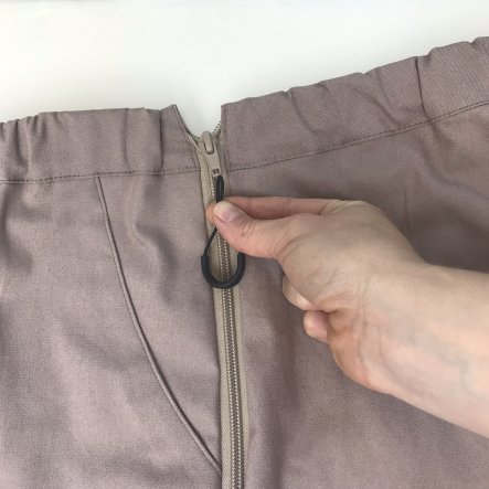 """De Ritshulp Bij DAPR Fashion gebruiken we een kunststoffen ritshulp. De ritshulp is vast te maken aan bijna alle ritssluitingen. Bijna omdat de rits wel een gaatje moet hebben om de ritshulp doorheen te doen. Door de rits vast te maken aan de broekrits zoals op de foto, gaat het open- en dichtdoen makkelijker. De rits is zo gevonden en met 1 vinger kan de rits dichtgetrokken worden. En met een duim weer open geduwd. Het fijne is, dat de rits """"plat"""" op het kledingstuk ligt. Je kunt kiezen voor een felle kleur die goed zichtbaar is. Of juist zwart voor een """"onzichtbare"""" ritshulp."""