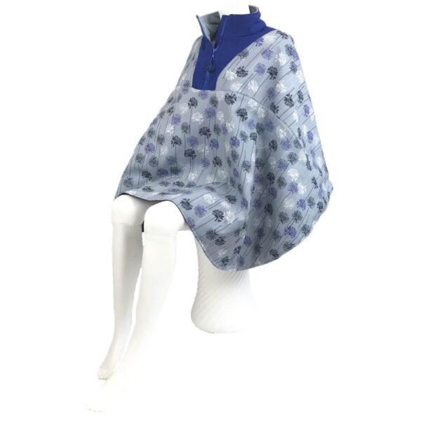 Schuin vooraanzicht van de lichtblauwe met blauwe en witte bloemetjes en kobaltblauwe kraag korte warme winddichte en waterafstotende rolstoelcape ROYAL BLOOM