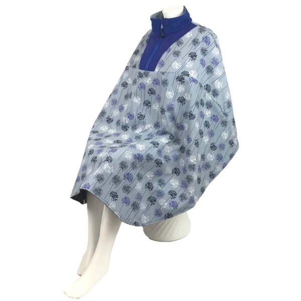 Schuin vooraanzicht van de lichtblauwe met blauwe en witte bloemetjes en kobaltblauwe kraaglange warme winddichte en waterafstotende rolstoelcape ROYAL BLOOM